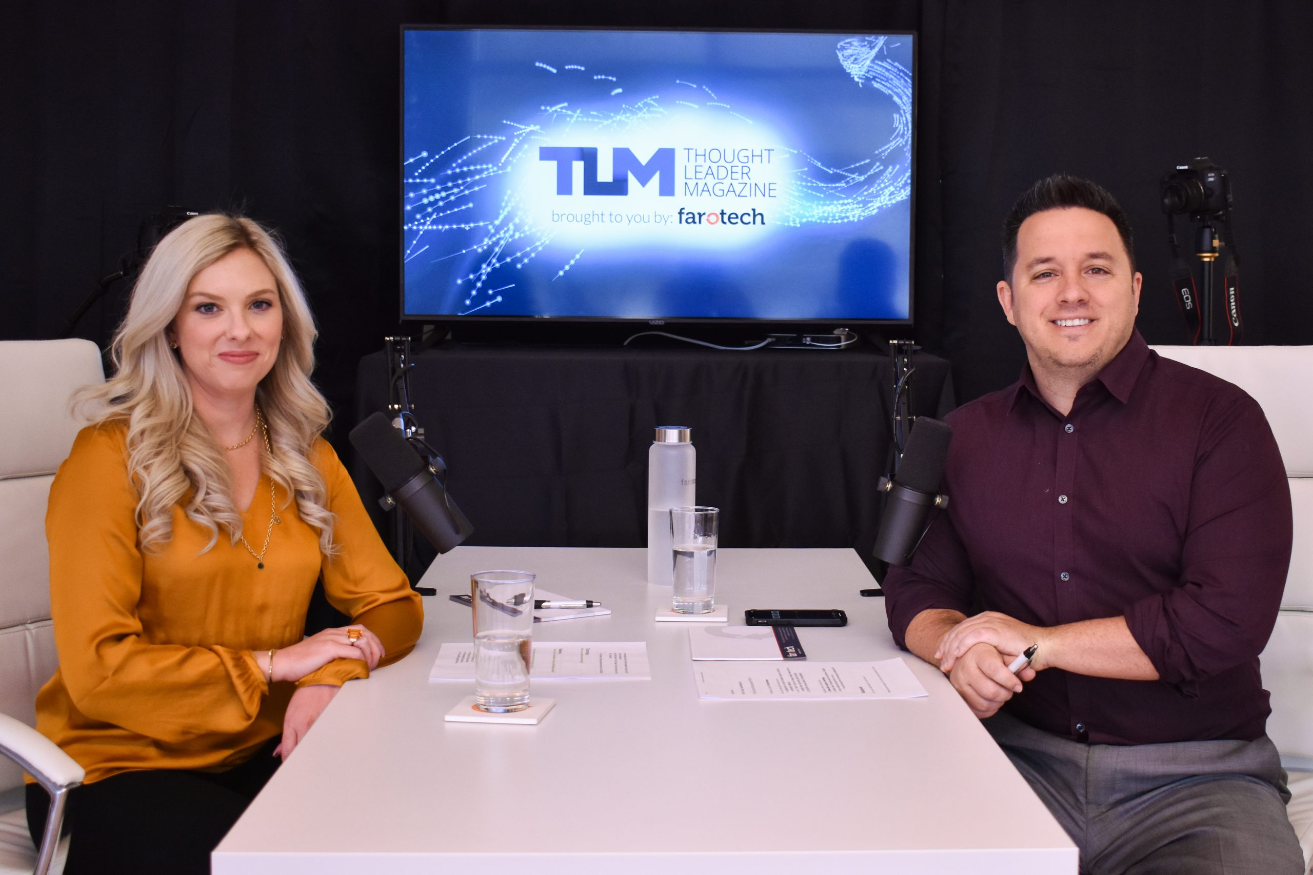 Chris and Emily sitting at a table recording a podcast